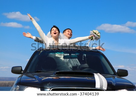 fiance and bride are glad standing in car - stock photo