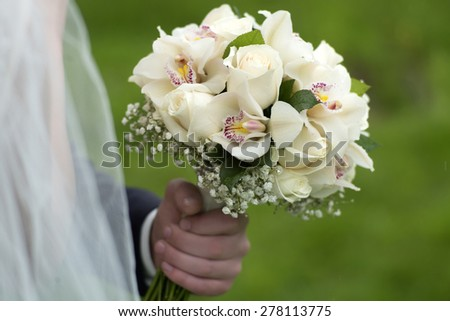 Fiance holding a delicate bouquet of roses and orchid in pastel colours outdoor on green holiday background, horizontal picture - stock photo