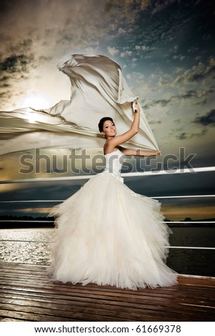 Fiance in the wind. Pretty lady in a wedding dress on deck.