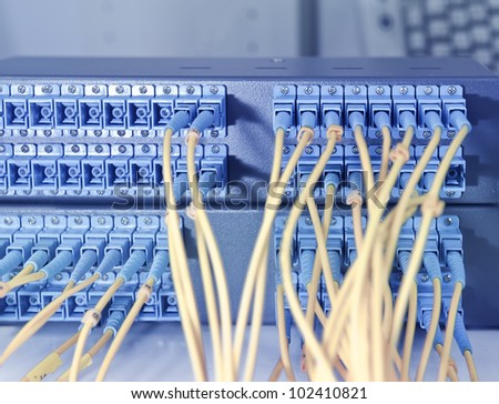 Fiber cables connected to servers in a datacenter - stock photo
