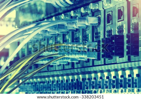 Fiber network switch with some yellow optical network cables - stock photo