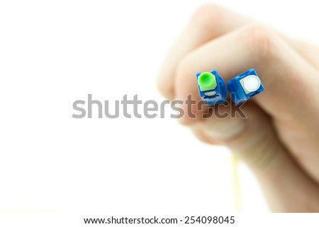 Fiber optic cable with blue patch cord connectors in hand isolated on white background - stock photo