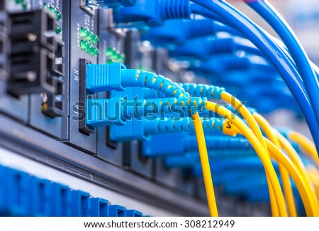 Fiber Optic cables connected to an optic ports - stock photo