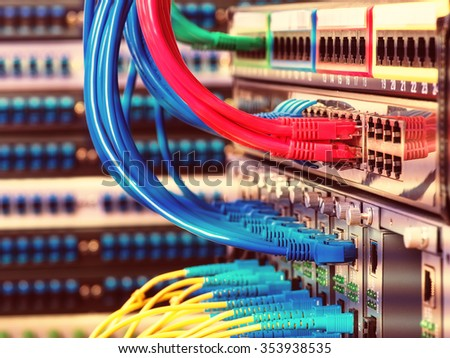 Fiber Optic cables connected to an optic ports and UTP Network cables connected to ethernet ports. - stock photo