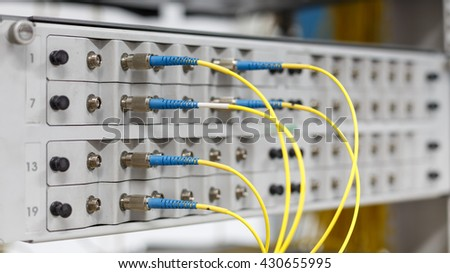 Fiber optical switch with connected FC cables in server room. - stock photo