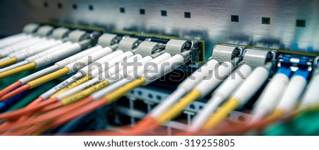 Fiber optical switch with connected FC cables in server room. Cross balance effect applied - stock photo