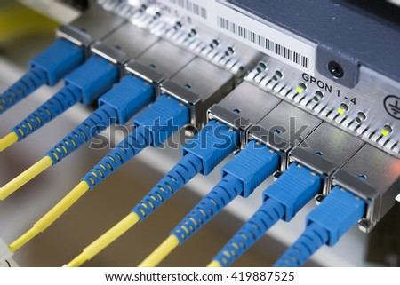 Fibre optic cable connected to an optic ports in a datacenter. - stock photo