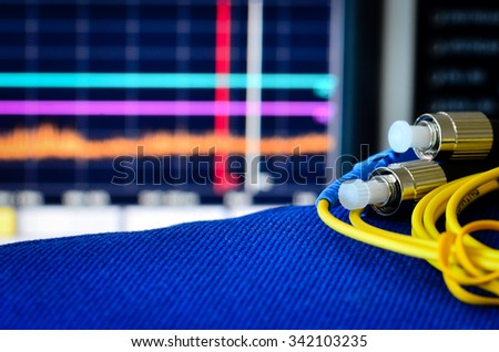 Fibre optic cable with spectrum analiser in the background - stock photo