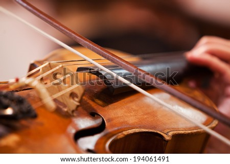 Fiddlestick on the strings of a violin closeup - stock photo