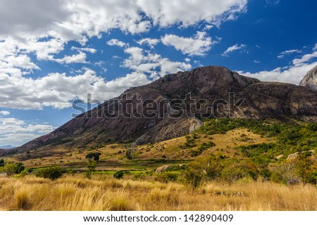 Field and rock, blue cloudy sky, amazing view