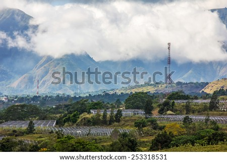 Field at mountain slope with blue sky - stock photo