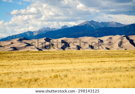 Field, Dunes, Mountains at Great Sand Dunes National Park - stock photo