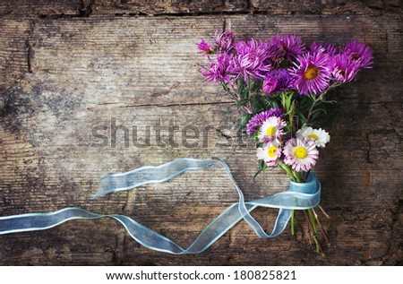 Field flowers on rustic wooden background/spring or summer background