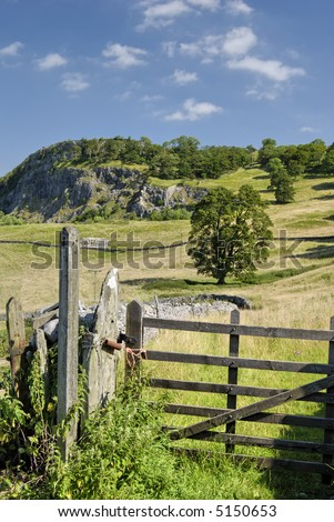 Field gate and footpath sign on meadows near Langcliffe in the Yorkshire Dales. Langcliffe scar is in the background - stock photo