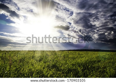field green grass and dramatic sunset cloudy sky - stock photo