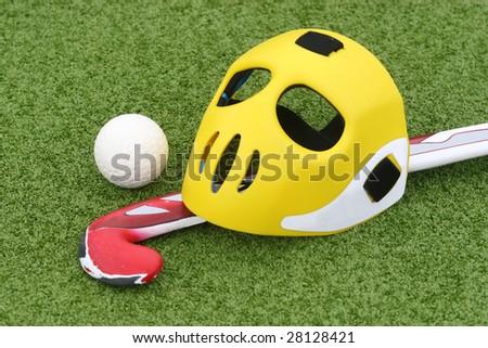 Field hockey equipment on green grass - stock photo