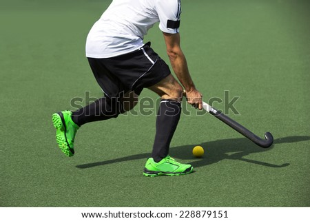 Field hockey player, in possesion of the ball, running over an astroturf pitch, looking for a team mate to pass to - stock photo
