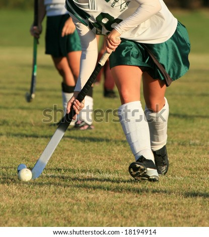Field hockey player with ball - stock photo