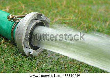 field hosepipe sprinkler grass - stock photo