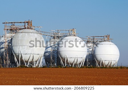 field of crude oil tanks on agriculture field - stock photo