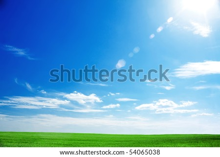 field of fresh green grass and bright blue sky with the sun causing lens flare - stock photo