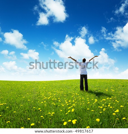 field of grass and happy young man - stock photo