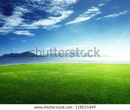field of grass and sea in sunset time, Seychelles, LaDigue island - stock photo