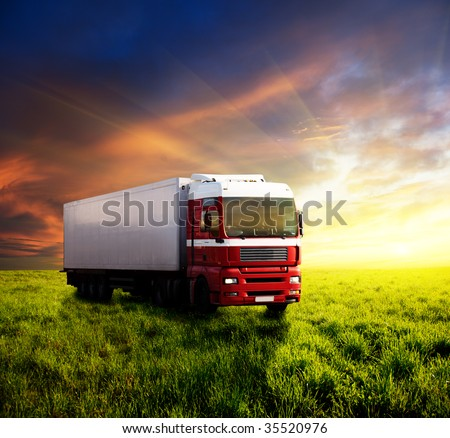 field of grass in sunset and truck - stock photo