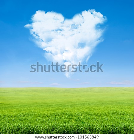 field of green grass over blue sky with clouds in shape of heart - stock photo