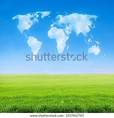 field of green grass over blue sky with world shaped clouds - stock photo