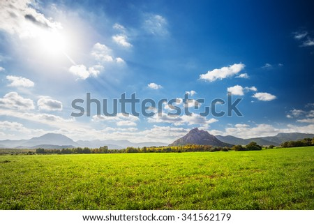 Field of green grass with mountains in the distance - stock photo