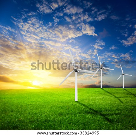 field of summer green geass and windmills - stock photo