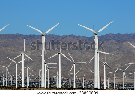 field of wind turbines in the desert with blue sky