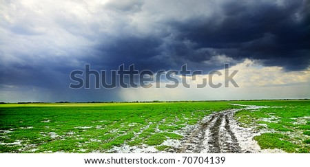 field road and dark clouds - stock photo