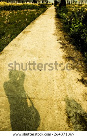 Field road and shadow of man on the road. - stock photo