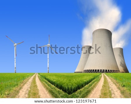 field way with nuclear power plant and wind turbines - stock photo