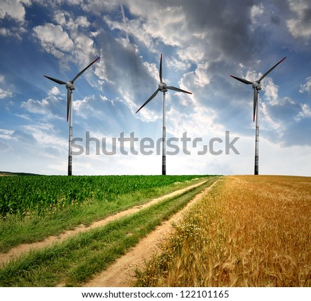 Field way with wind turbines - stock photo