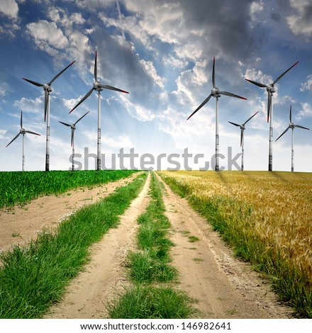 Field way with wind turbines in the sunset - stock photo