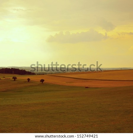 field with a tractor - stock photo