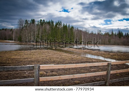 Field with a wooden fence in the foreground - stock photo