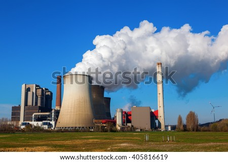 field with fossil-fuel power station - stock photo