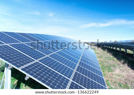 Field with many solar cells in front of a blue sky