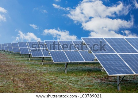 Field with many solar cells in front of a blue sky with clouds - stock photo
