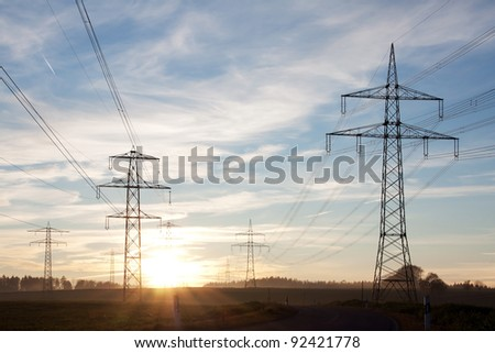 Field with power transport lines in the dusk - stock photo