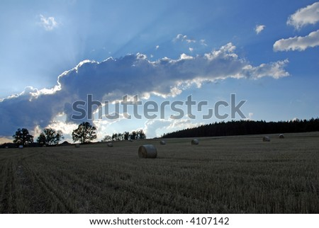 Field with straw rolls and dramatic sky