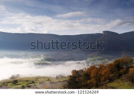 fields and mountains on a cold morning, fog in the valley and clouds in the sky - stock photo