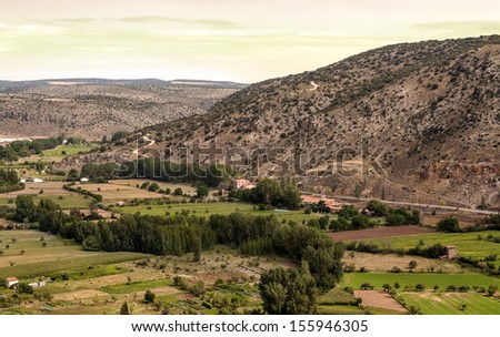 Fields of Albarracin with trees you can see the mountain in a cloudy day. - stock photo