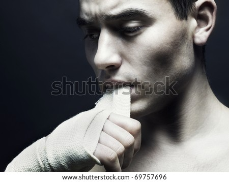 Fierce athlete with a bandage in his mouth - stock photo
