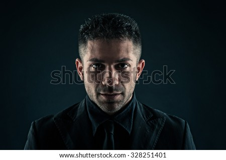 Fiery man close up portrait against dark background.  - stock photo