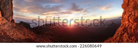 Fiery sunrise over a panoramic mountain landscape framed by two steep rocky cliffs lit by the glow of the sun for a dramatic scene of natural beauty - stock photo
